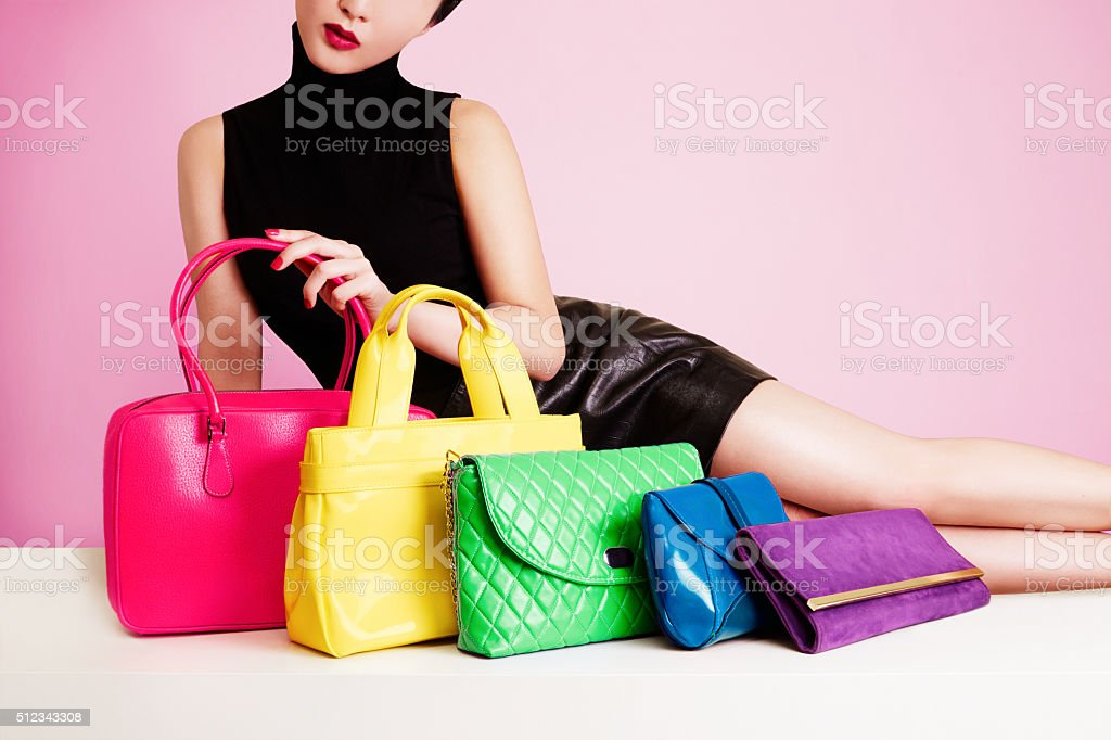 Woman with many colorful handbags purses. stock photo