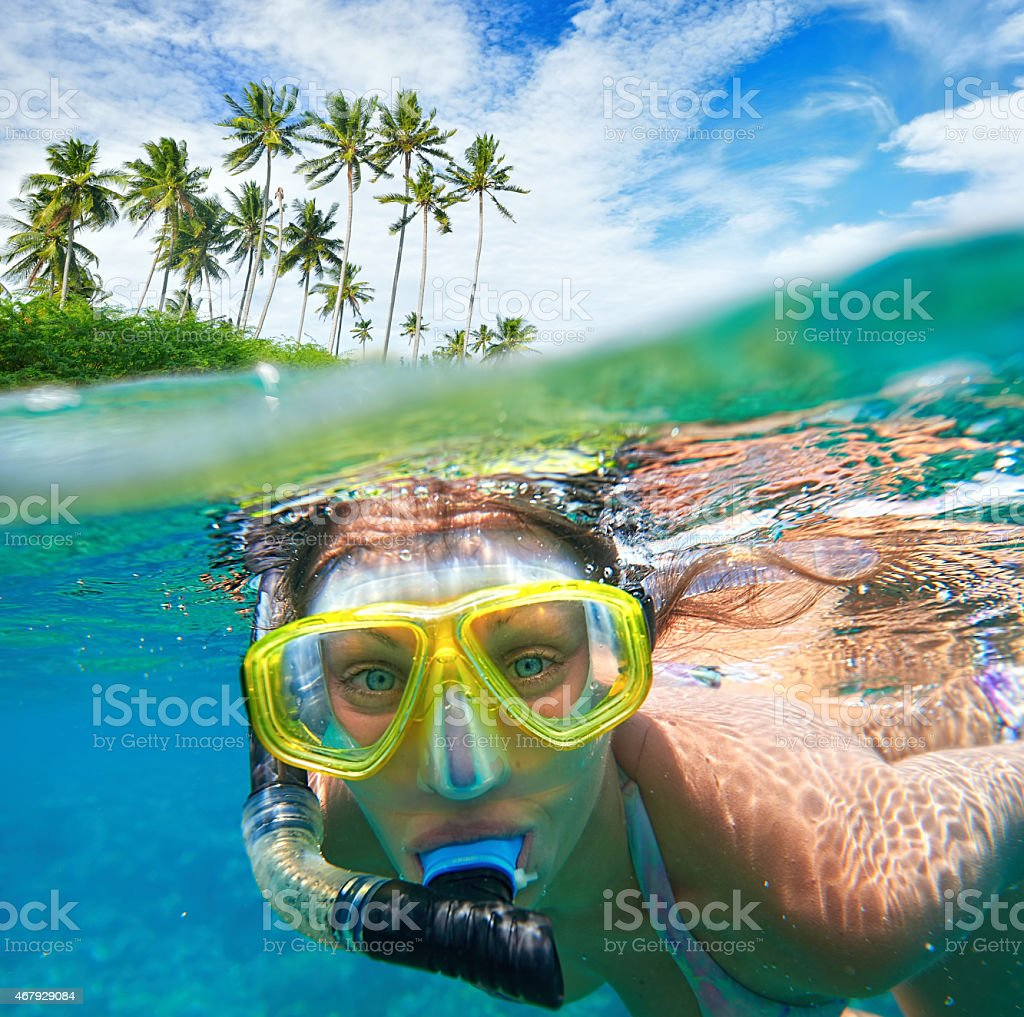 Woman with mask snorkeling in clear water. stock photo