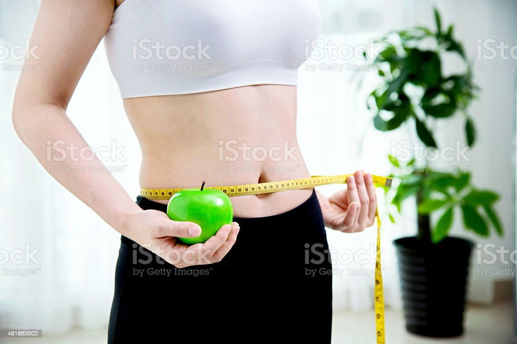 Woman with measuring tape and apple stock photo