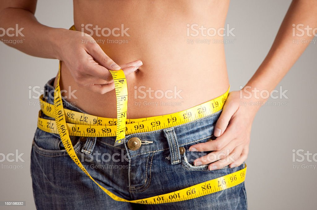 Woman with measuring tape around her waist royalty-free stock photo