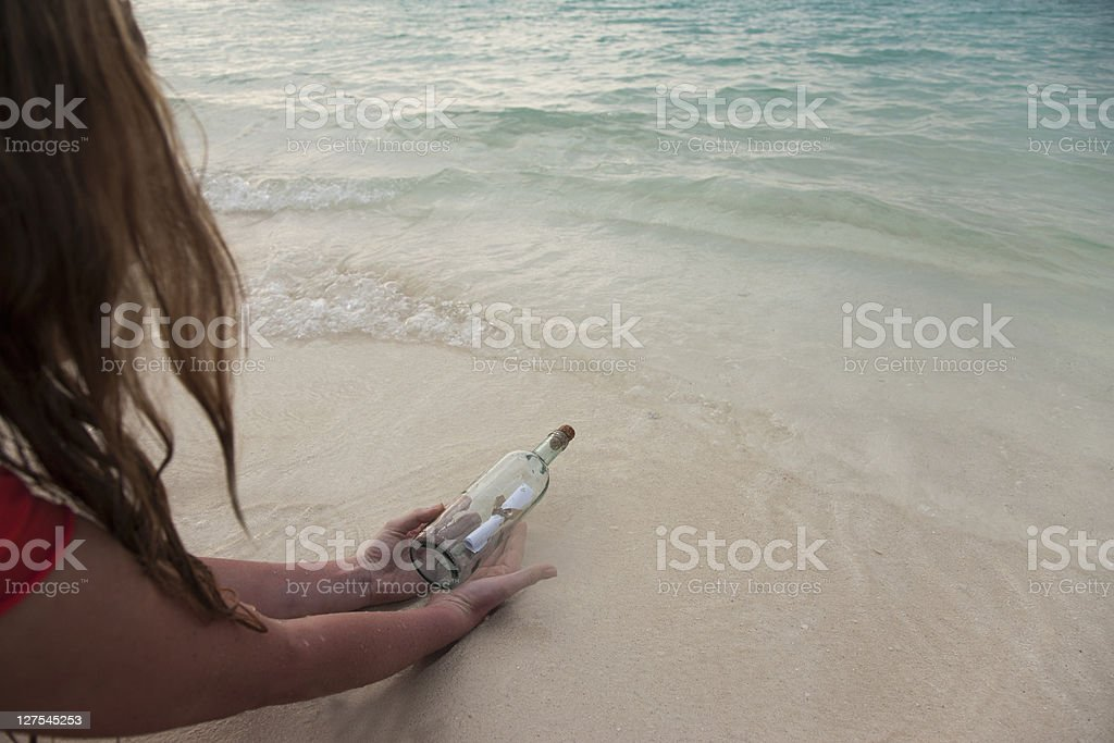 Woman with message in a bottle at beach stock photo