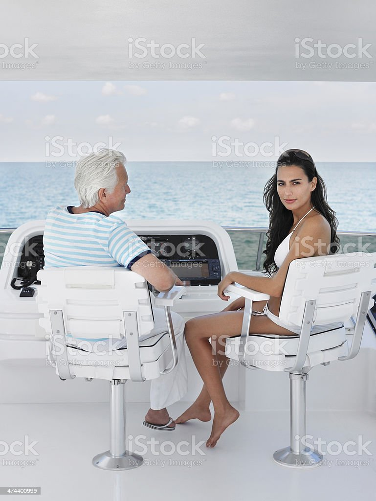 Woman With Middle Aged Man Sitting At Helm Of Yacht stock photo