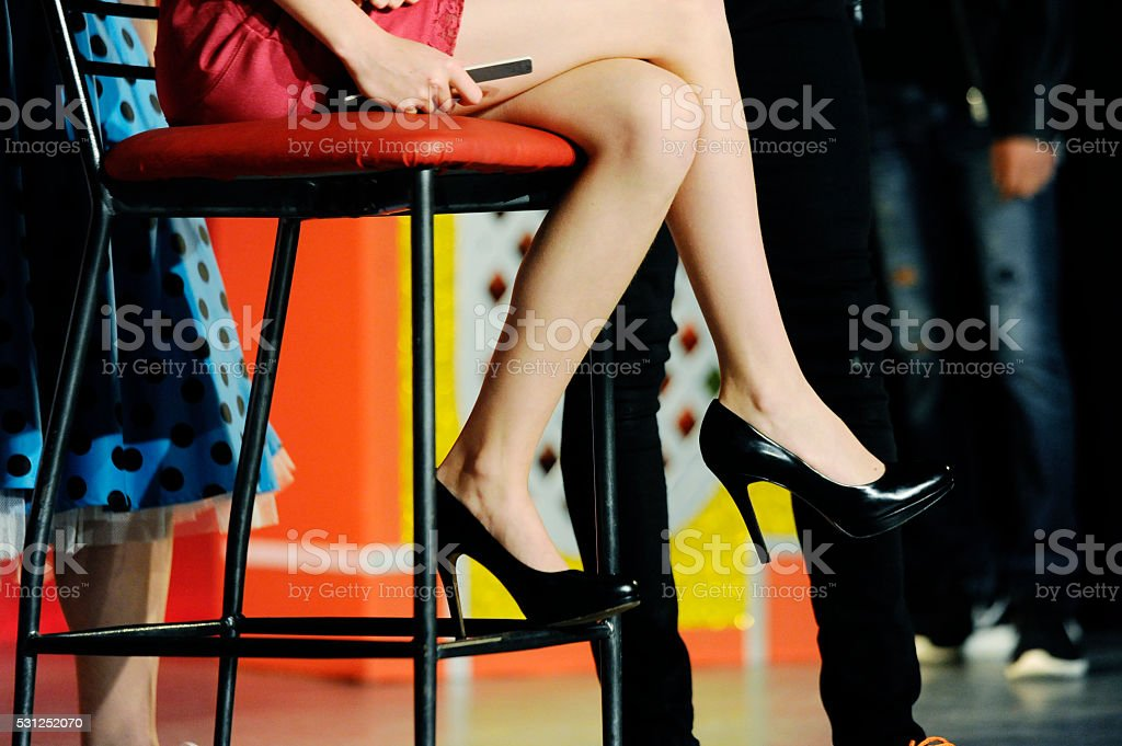 Woman with mini skirt and black high heels showing legs stock photo