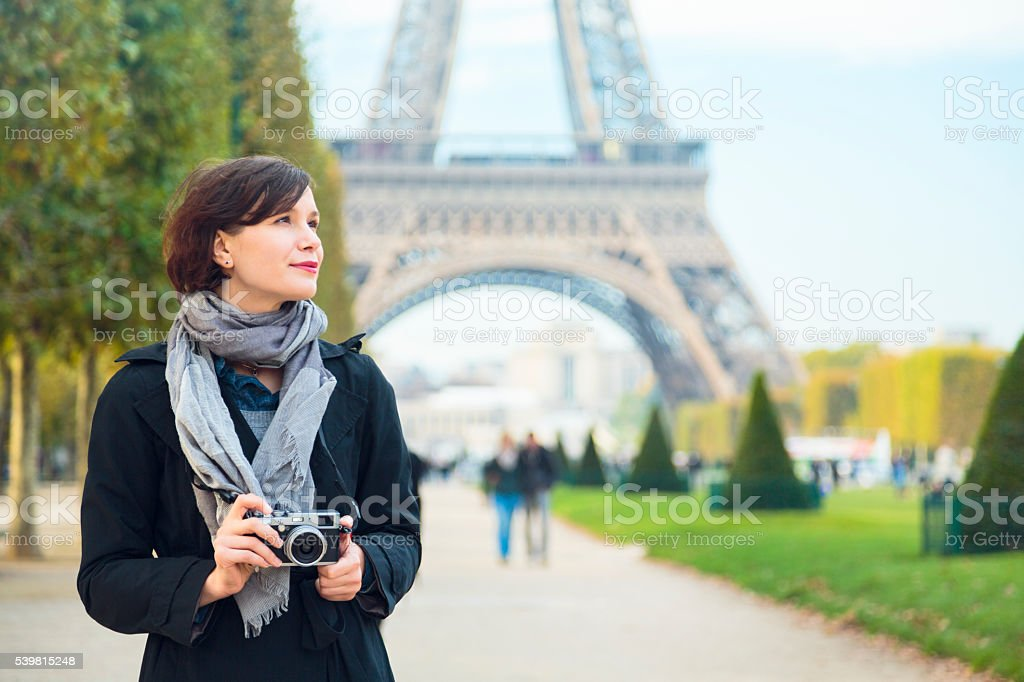 Woman with mirrorless camera in front of Eiffel tower, Paris stock photo