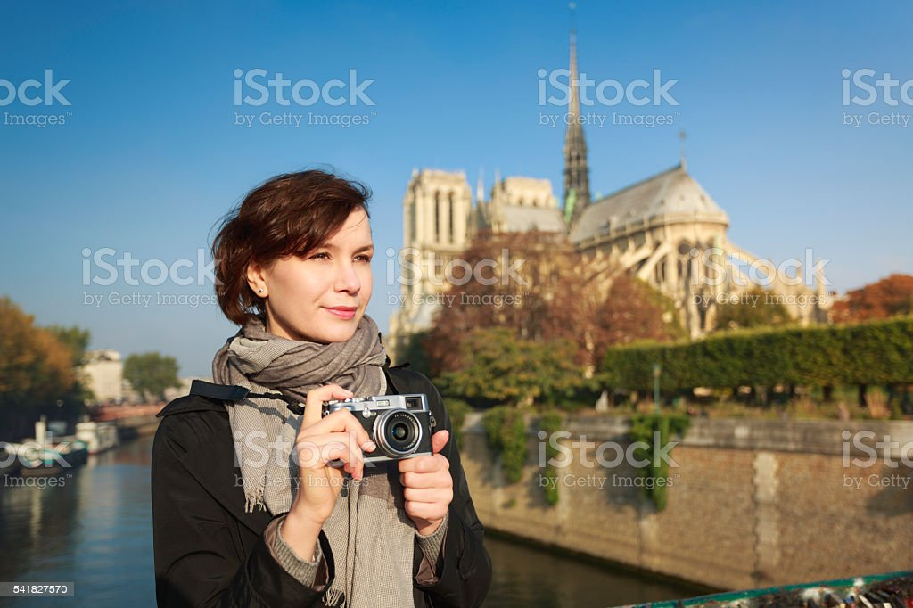 Woman with mirrorless camera in front of Notre Dame, Paris. stock photo