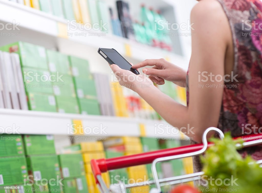 Woman with mobile at supermarket stock photo