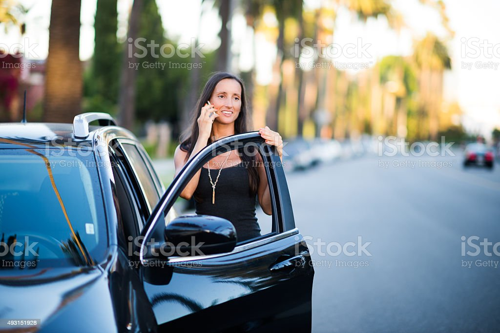 Woman with mobile phone next to black SUV stock photo