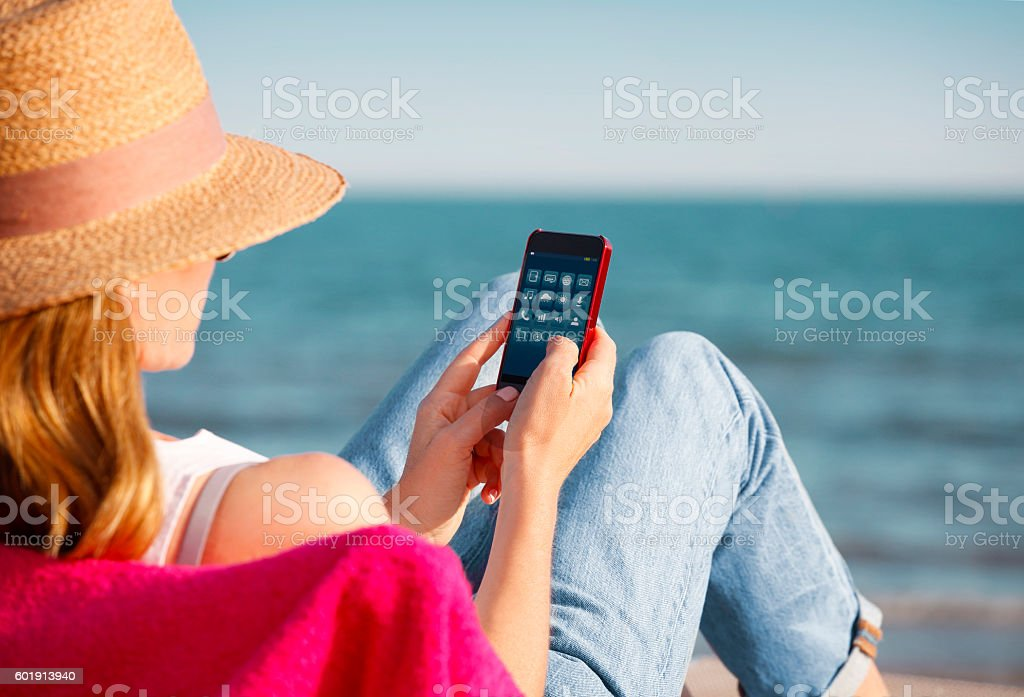 Woman with mobile phone on the beach stock photo