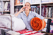 Woman with mobile shopping new blanket and coverlet