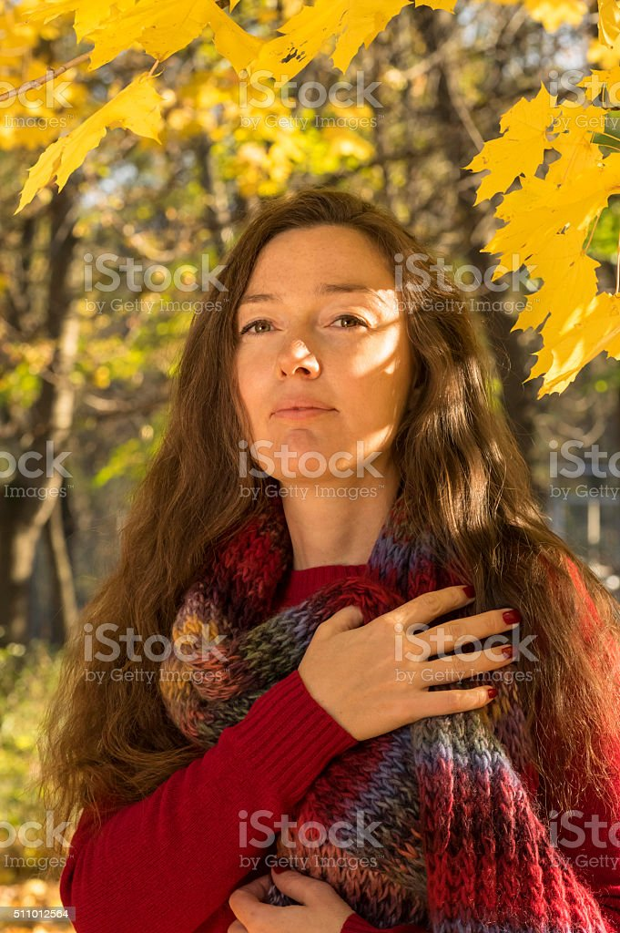 Woman with multicolored scarf at autumn forest stock photo