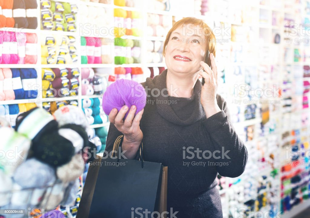 Woman  with needlework accessories and talking on phone stock photo