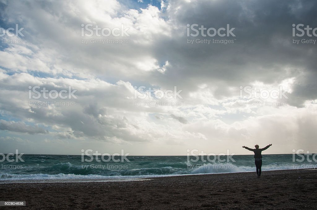 woman with open arms under dramatic sky stock photo