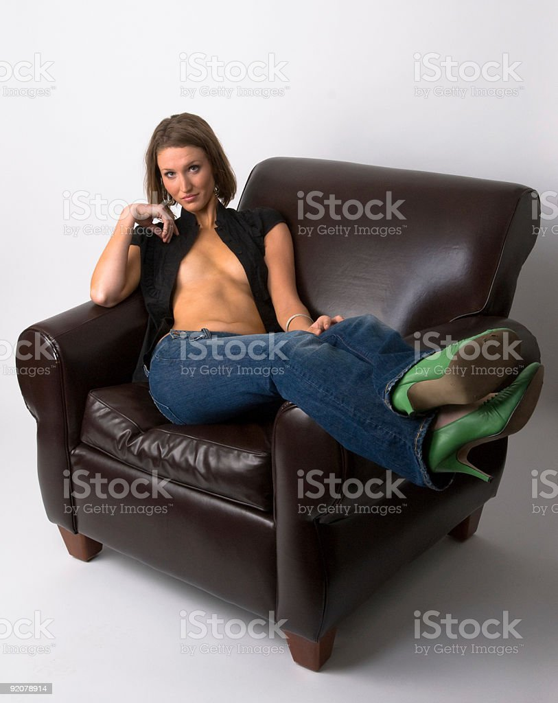 woman with open shirt in leather chair royalty-free stock photo
