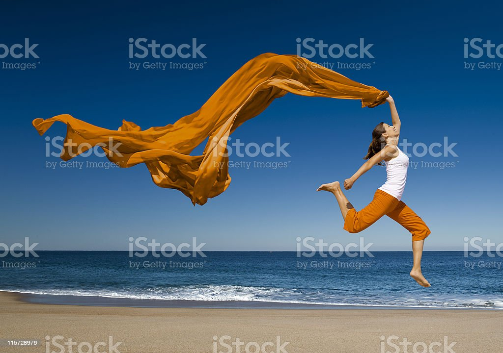 Woman with orange scarf jumping in the beach stock photo