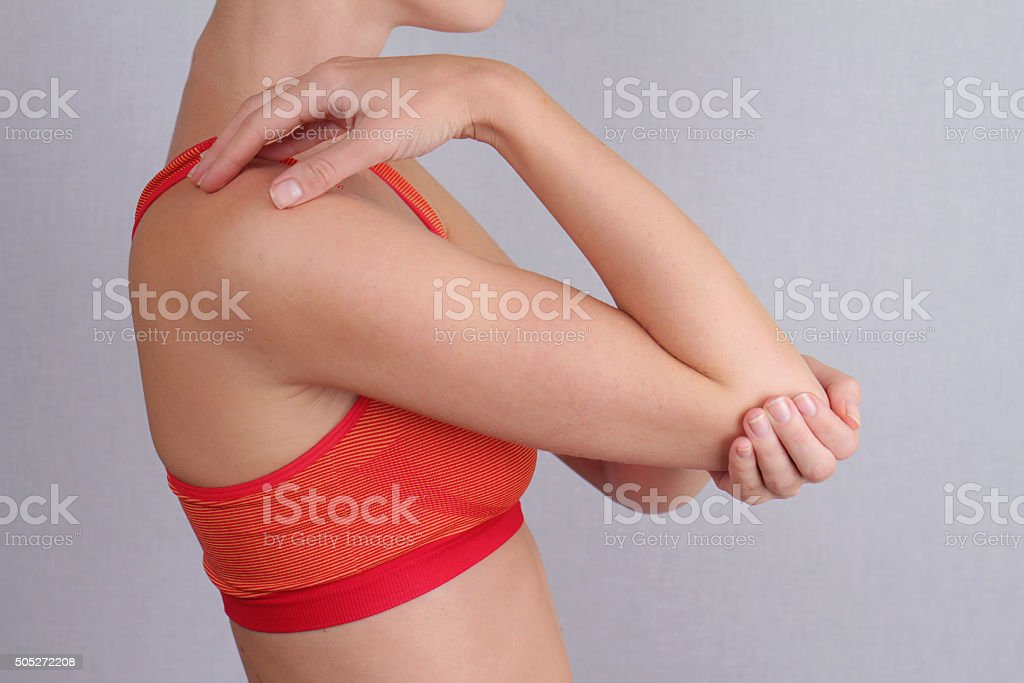 Woman With Pain In Elbow. Pain relief concept stock photo