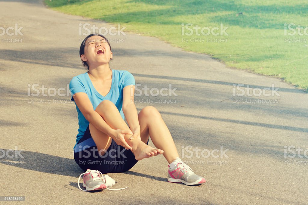 Woman with painful ankle sprain stock photo