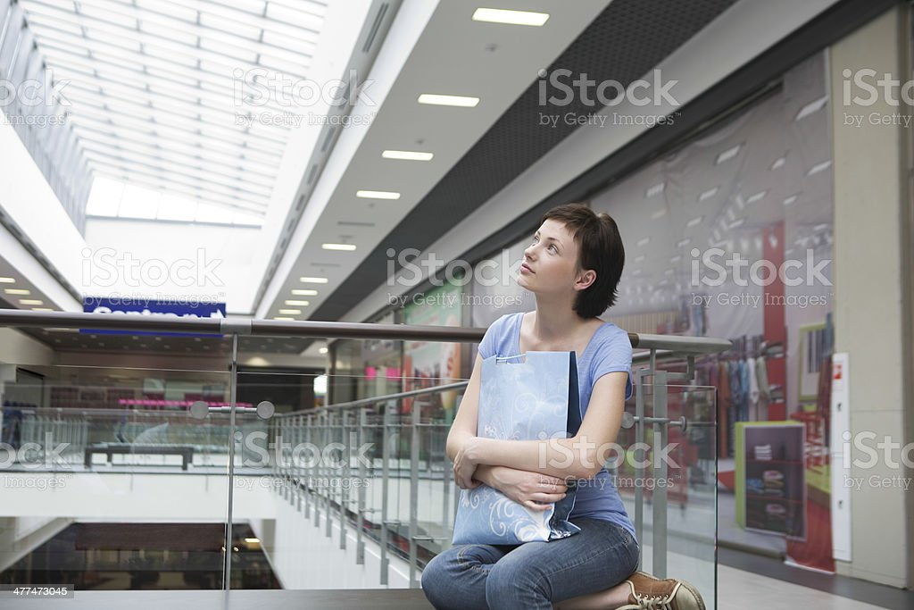 Woman With Paper Bag Looking Up In Shopping Centre royalty-free stock photo