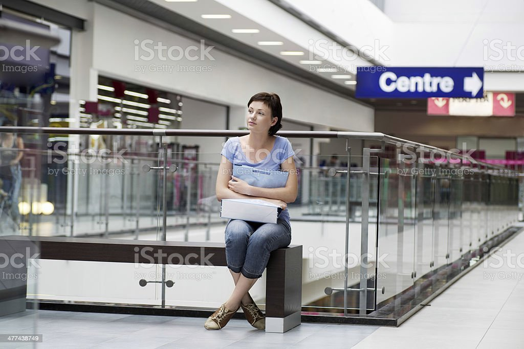 Woman With Paper Bag Sitting In Shopping Centre royalty-free stock photo
