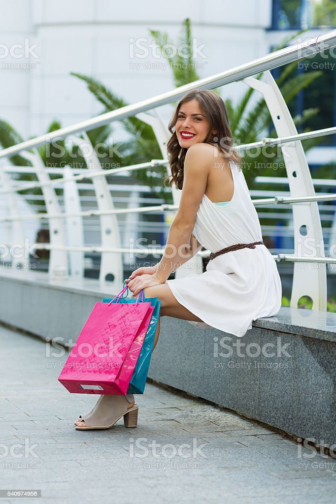 Woman with paper bags after shoppig in summer city stock photo