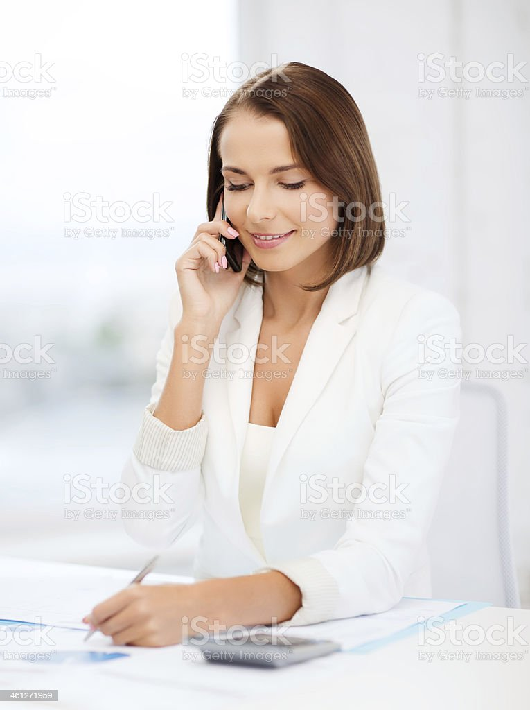 woman with papers, calculator and smartphone stock photo