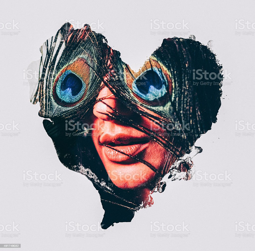 Woman with peacock feathers over her eyes in heart shape stock photo