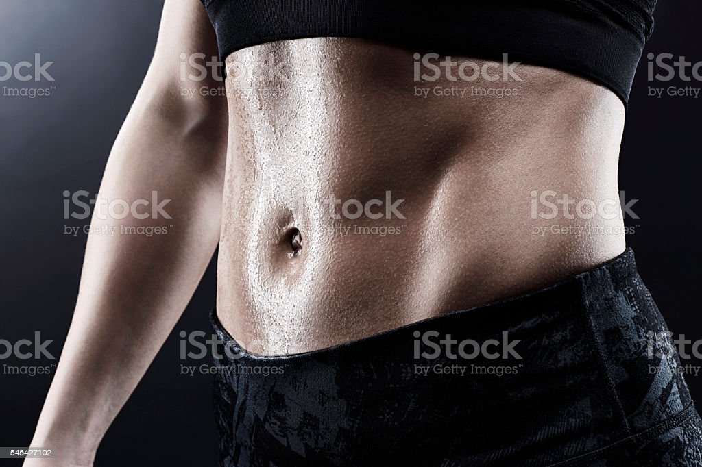 Woman with perfect abdomen muscles sweating after workout stock photo