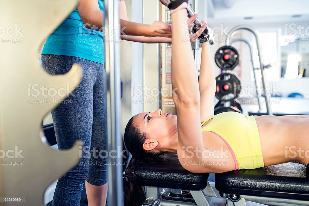 Woman with personal trainer bench pressing with weights, gym stock photo