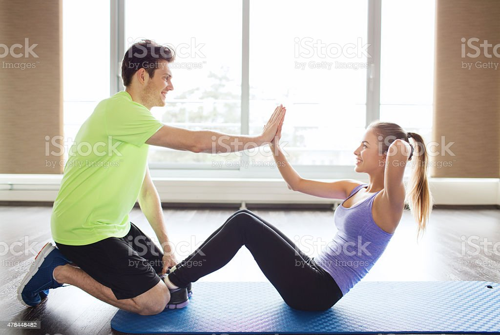 woman with personal trainer doing sit ups in gym stock photo