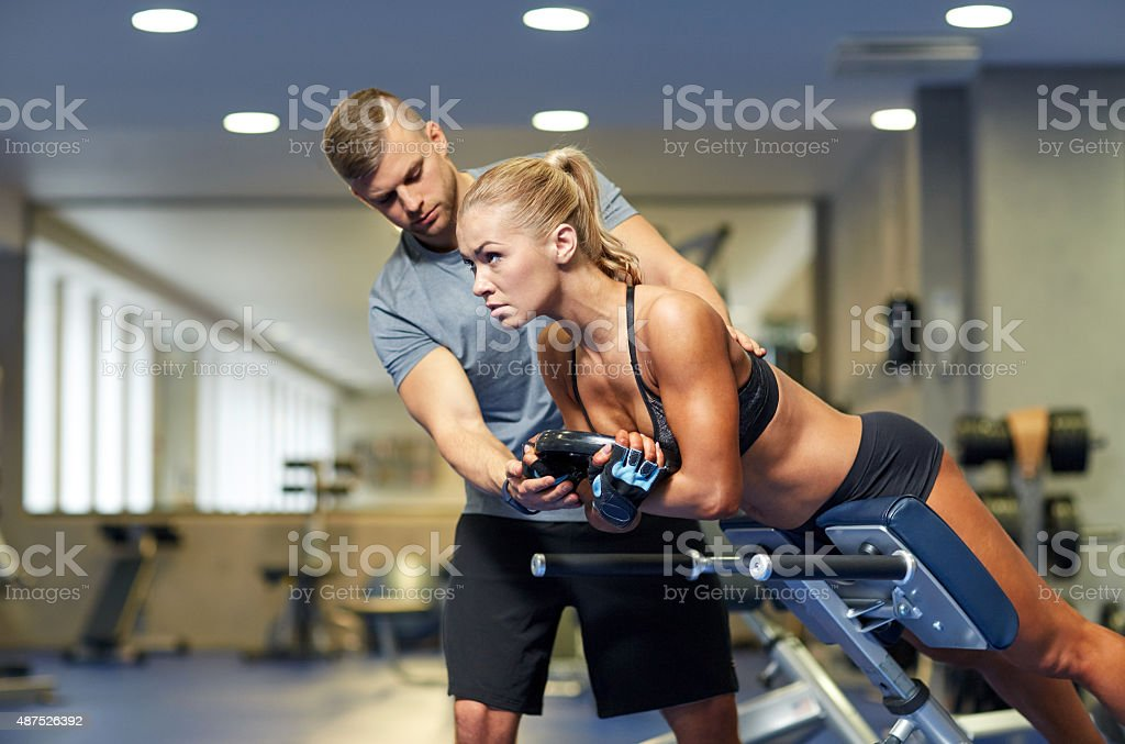 woman with personal trainer flexing muscles in gym stock photo