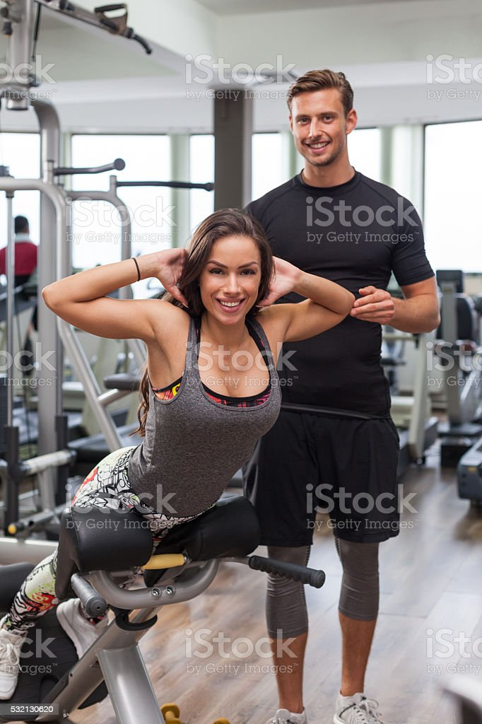 woman with personal trainer  in gym stock photo