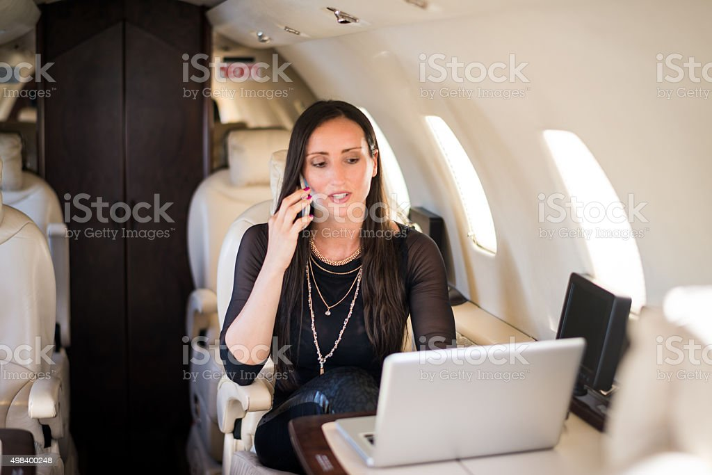 Woman with phone in private jet airplane stock photo
