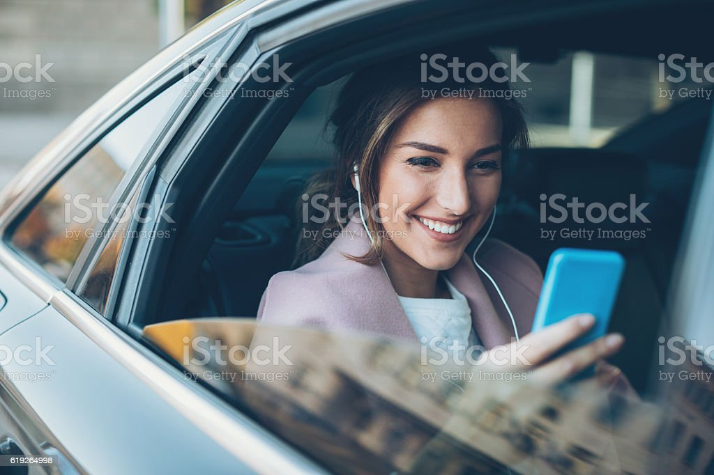 Woman with phone on the back seat of a car stock photo