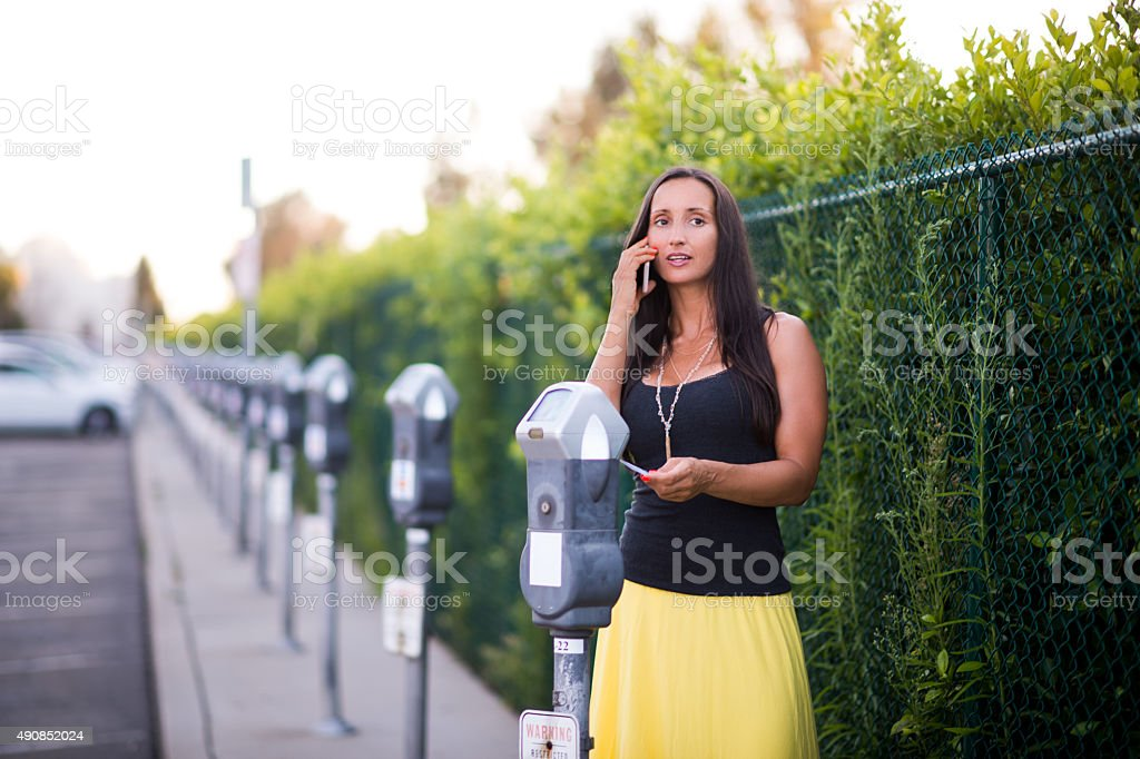 Woman with phone standing next to parking meter stock photo