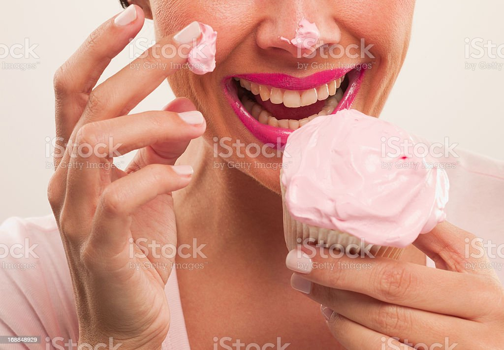 Woman with pink lipstick and frosting on nose eating cupcake royalty-free stock photo