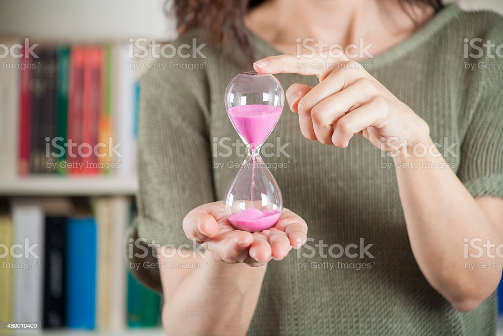 woman with pink sand clock stock photo