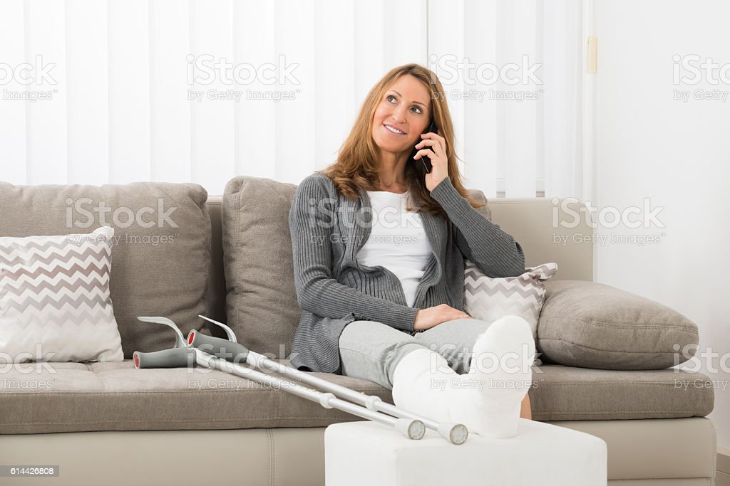 Woman With Plastered Leg Talking On Mobile Phone stock photo
