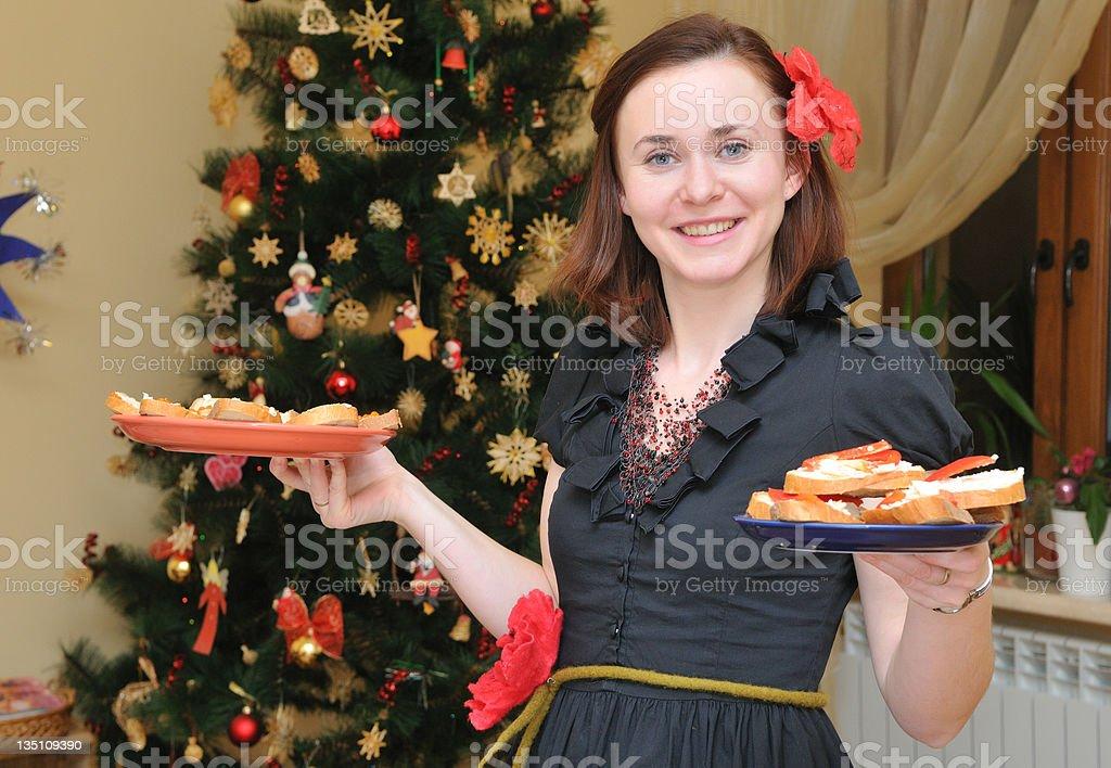 woman with plate near Christmas-tree stock photo