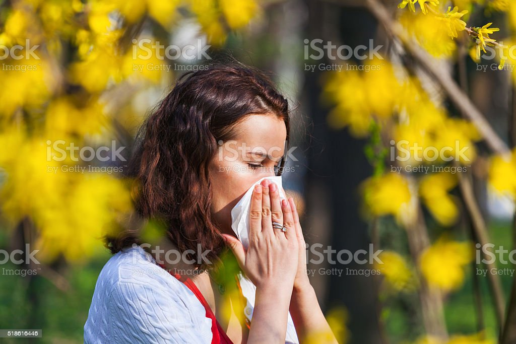 Portrait of a young brunette woman blowing her nose when standing...