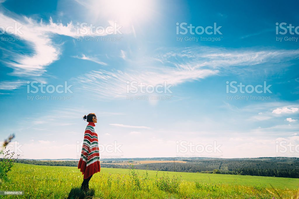 woman with poncho in summer landscape at early morning stock photo