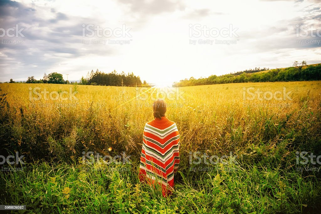 woman with poncho standing in summer field stock photo