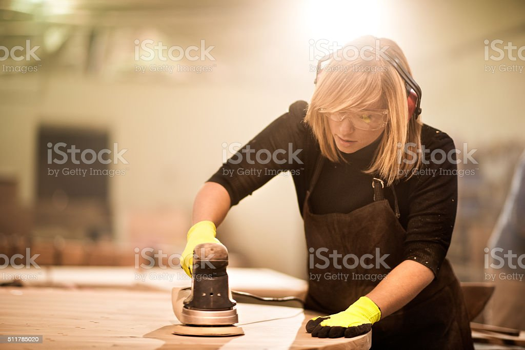 Woman with power sander at work stock photo