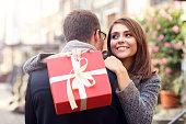 Woman with present giving hug to her man