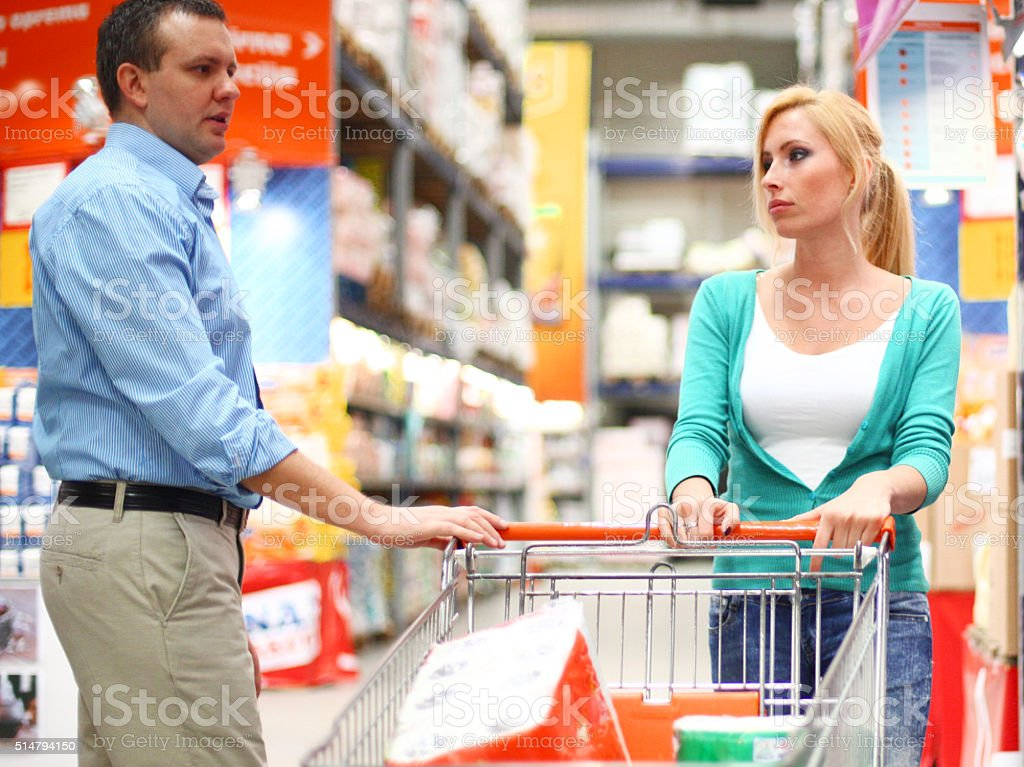 Woman With Product Smiling While Man Shopping In Background stock photo