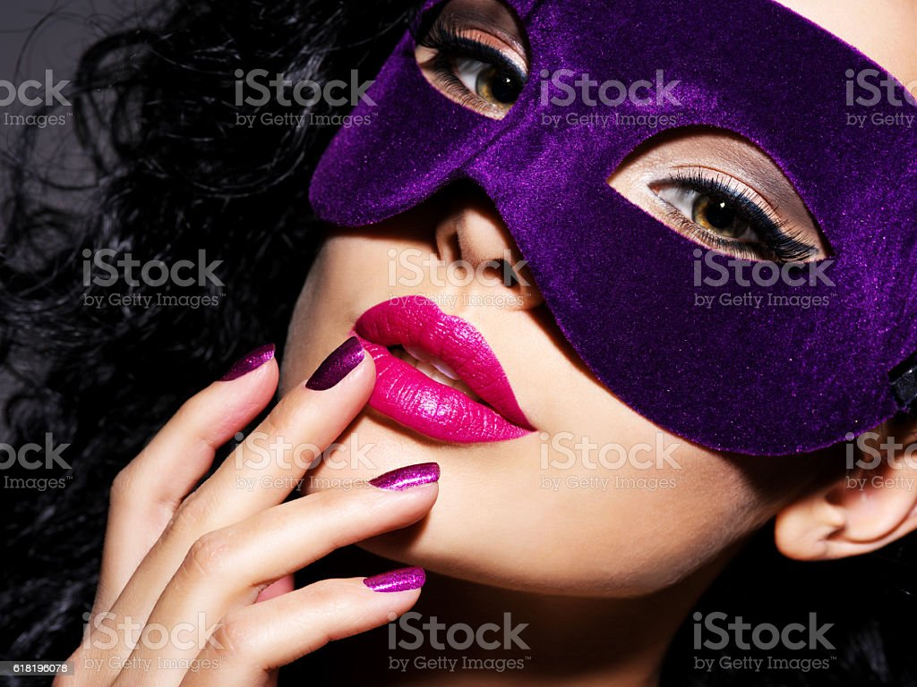 woman with purple nails and theatrical mask on her face stock photo