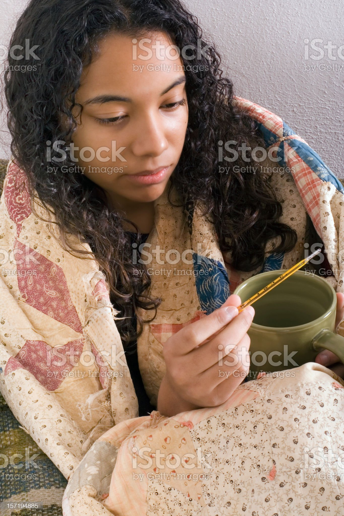 Woman with quilt over shoulders holding mug and thermometer royalty-free stock photo