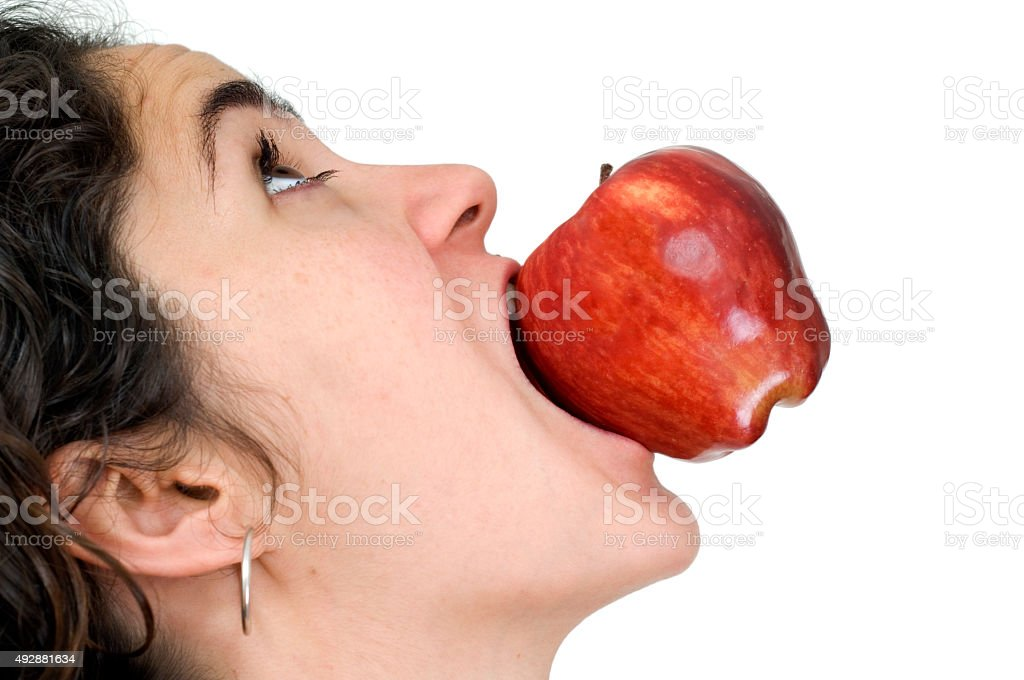 Woman with red apple in mouth stock photo