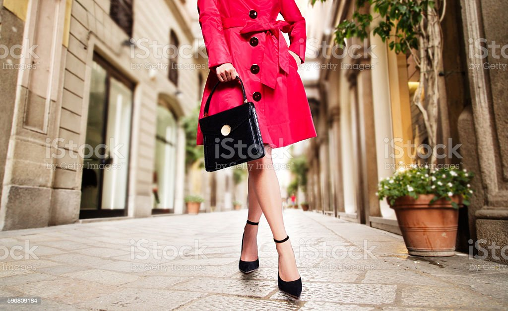 Woman with red coat,black handbag,shoes in town. stock photo