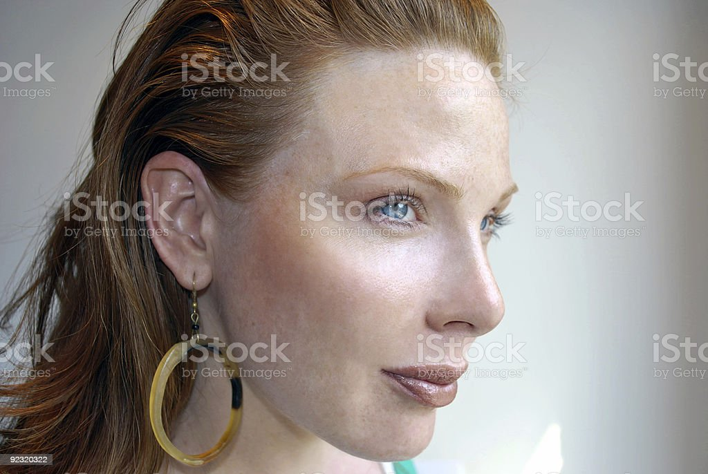 Woman with red hair and blue eyes wearing hoop earring stock photo