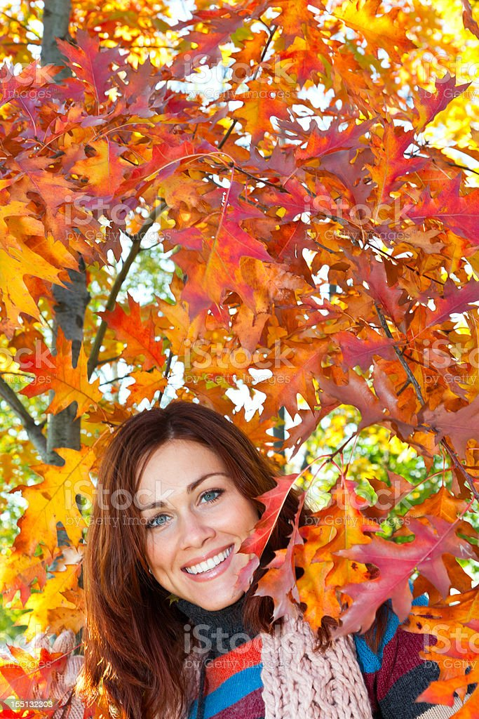Woman with red hair between autumn leaves royalty-free stock photo