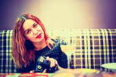 Woman with red hair hold camera and sitting at cafe